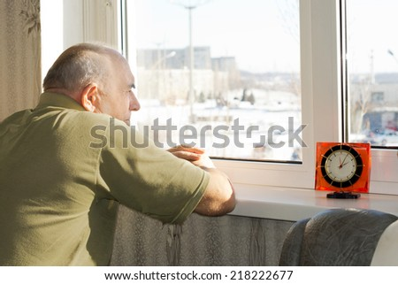 Bored senior man waiting patiently for time to pass as he stands staring disconsolately out of a window on a sunny day waiting for someone to arrive for a visit - stock photo