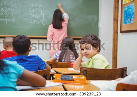Bored student looking away from board at the elementary school - stock photo