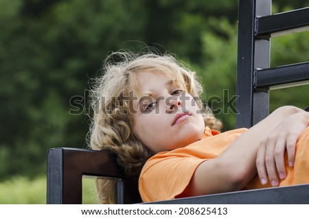 Bored teen laying across a park bench - stock photo