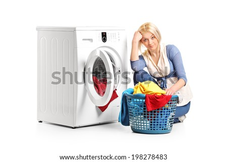 Bored woman sitting by a washing machine and doing laundry isolated on white background - stock photo