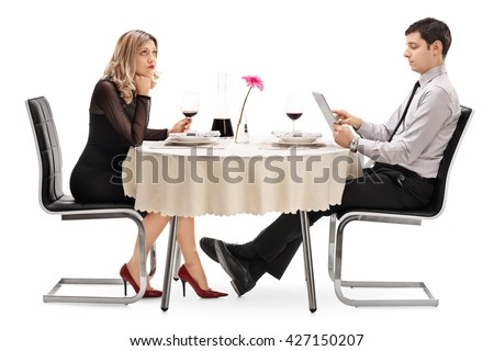 Bored woman sitting on a date with a man playing on a tablet isolated on white background - stock photo