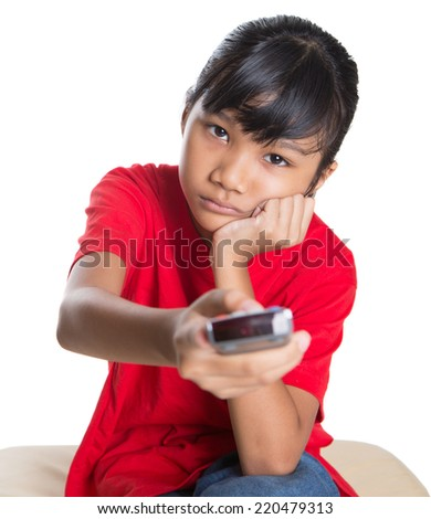Bored young Asian girl with television remote control device over white background - stock photo