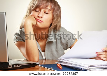 Bored young businesswoman at her desk against grey background - stock photo