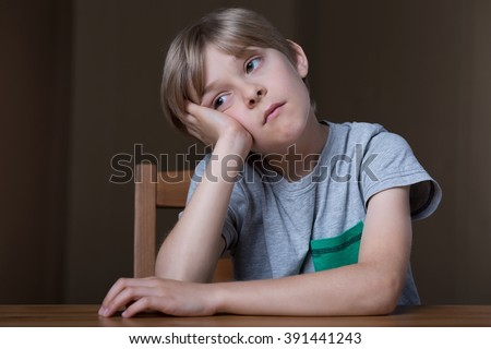 Bored young kid doing nothing but sitting - stock photo
