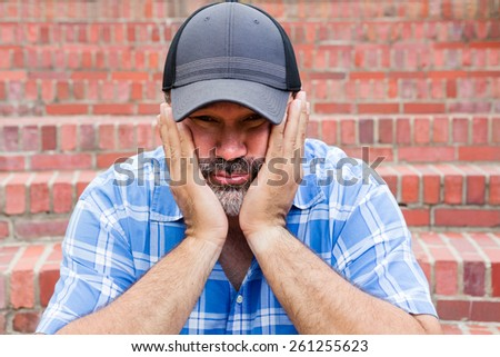 Boredom - the enemy of human happiness in a conceptual image of a middle-aged man with a goatee sitting resting his chin in his hands with a glum expression staring at the camera against a brick wall - stock photo