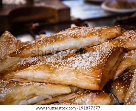 Borek (puff pastry pie with cheese coated with sesame seed) served in traditional oriental restaurant. Selected focus on the sesame seeds of the closest burek. - stock photo