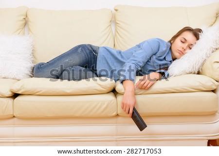 Boring film. Girl sleeping on sofa ta home in front of TV. - stock photo