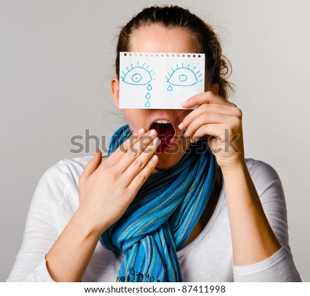 boring woman is holding paper with drawn tears - stock photo