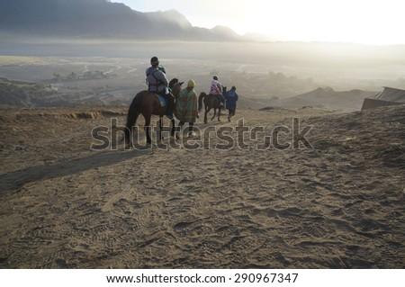 BORMO - JUNE 13, 2015: Tourist horseback riding during sunrise on June 13 2015 at  Mount Bromo Indonesia - stock photo