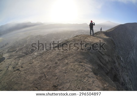 BORMO - JUNE 13, 2015: Tourist taking pictures at top of Mount Bromo on June 13 2015 at Bromo Tengger Semeru National Park, Indonesia. - stock photo