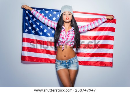 Born in America. Beautiful young black woman carrying American flag while standing against grey background  - stock photo