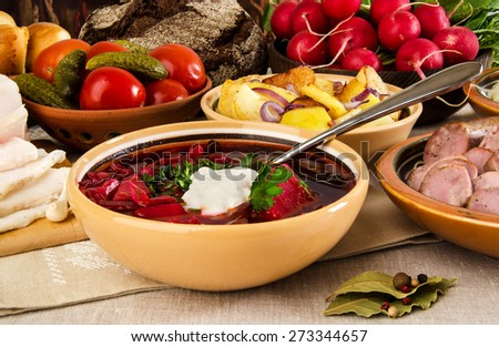 Borscht soup Ukrainian national red beet Buriak with bacon fried potatoes pickled cucumbers and tomatoes, bread and sausage salo - stock photo