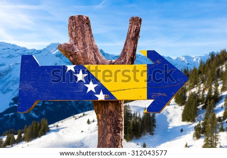 Bosnia and Herzegovina Flag wooden sign with winter background - stock photo