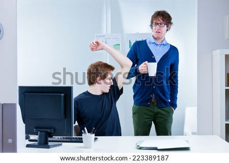 boss disgusted because of body odour coming from employee's pit stains and lack of workplace hygiene - stock photo