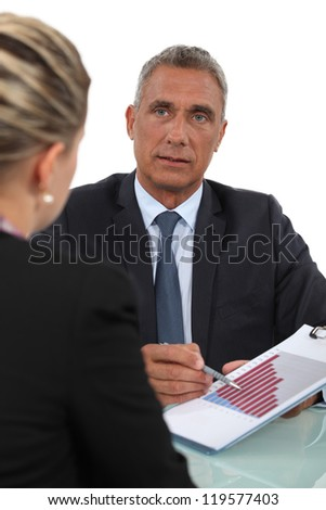 Boss explaining financial results to female employee - stock photo