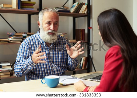 boss explaining something to young worker in his office - stock photo