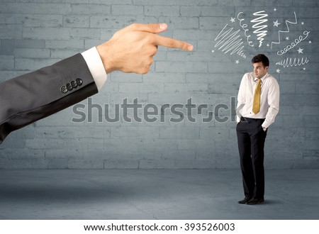 Boss firing employee concept with a huge hand pointing at confused business person illustrated by drawn lines in front of grey brick wall - stock photo