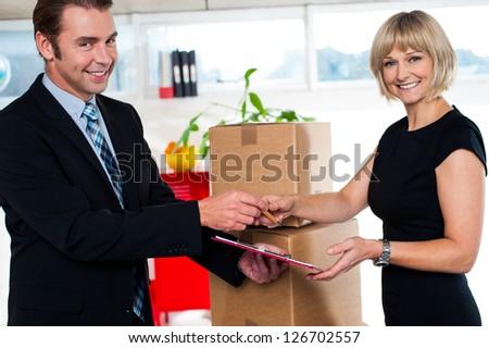 Boss handing over receipt packed cartons to his secretary. Indoor office shot. - stock photo