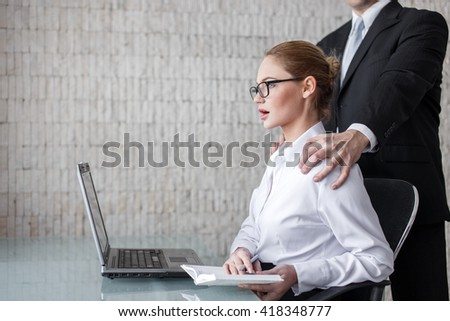 Boss put hands on secretary in office, sexual harassment - stock photo
