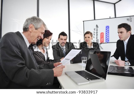 Boss reading report at business meeting - stock photo