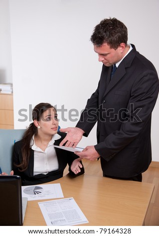 Boss showing dissatisfaction with his secretary's work - stock photo