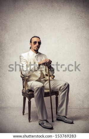 boss sitting on a chair dressed in white suit with stick and sunglasses - stock photo
