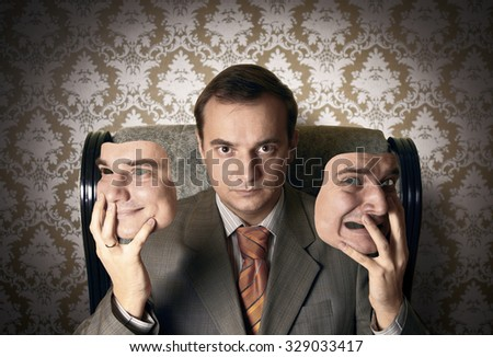 Boss sitting on the armchair, holding his face masks. Creative concept. - stock photo
