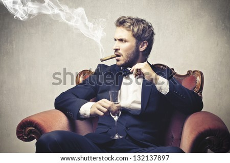 boss smokes cigar with a glass of champagne - stock photo