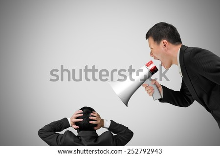 Boss using megaphone yelling at his employee with concrete wall background - stock photo