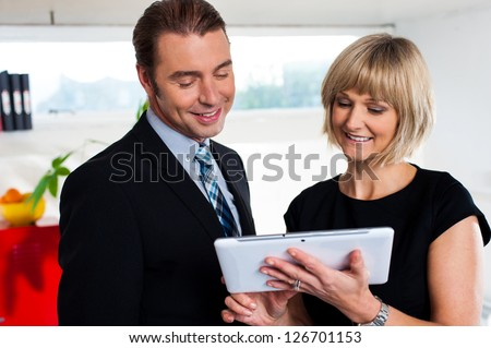 Boss with female secretary busy reviewing appointments saved on tablet device, office background. - stock photo