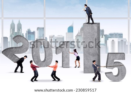 Bossy businessman commanding his employees to arrange number 2015 - stock photo