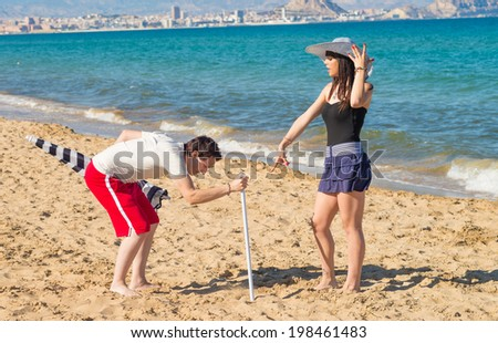 Bossy girl ordering her boyfriend around to set up  a sunshade on the beach - stock photo