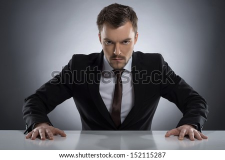 Bossy man. Angry young man in formalwear looking at camera while sitting at the table isolated on grey - stock photo