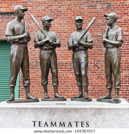 BOSTON, MA - JUNE 4: The statues of Ted Williams, Bobby Doerr, Johnny Pesky, and Dom Dimaggio attract hundreds of baseball fans to the Fenway Park in Boston, MA for souvenir photos on June 4, 2013. - stock photo
