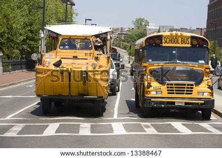 "Boston, MA May 29th, 2008:  Boston Duck Tours ""Ducks"" - converted WWII era DUKW amphibious transport next to a yellow school bus. - stock photo"