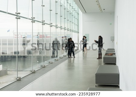 BOSTON, USA - OCTOBER 14; four young women taking photos and selfies in a hallway with Boston city background on October 14, 2014 in Boston USA . The girls are   in Institute of Contemporary Art. - stock photo