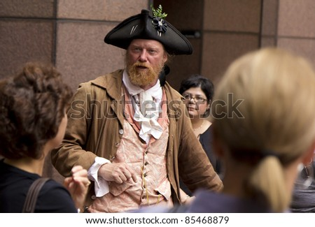 BOSTON, USA - SEPTEMBER 25: An unidentified man dressed in colony-time clothes guides tourists along the Freedom Trail in Boston, MA on Sept. 25, 2011. He tells the history of the city and information on sight seeing. - stock photo
