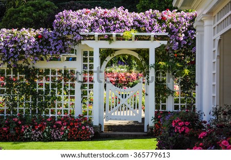Botanical garden white fence with gate and blooming flowers - stock photo