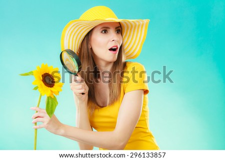 Botanist woman funny face expression in yellow hat examining flower looking through magnifying glass on blue background - stock photo