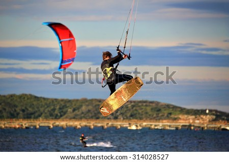 BOTANY BAY, AUSTRALIA - AUGUST 1, 2015; Kite surfers on Botany Bay, one manoeuvres high in the air - stock photo