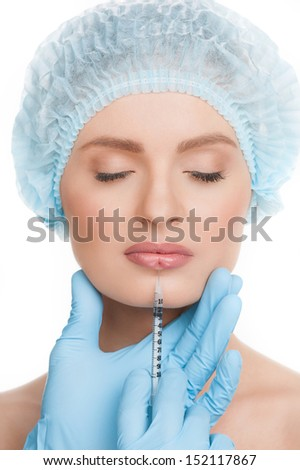 Botox injection. Portrait of beautiful young woman in medical headwear keeping eyes closed while doctors hands in gloves making a botox injection in her lips - stock photo