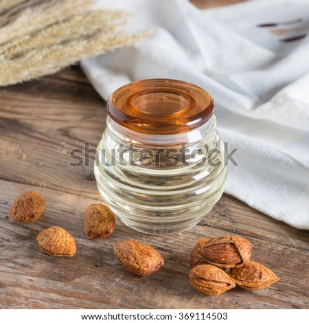 Bottle almond oil and almond kernel on wood background - stock photo