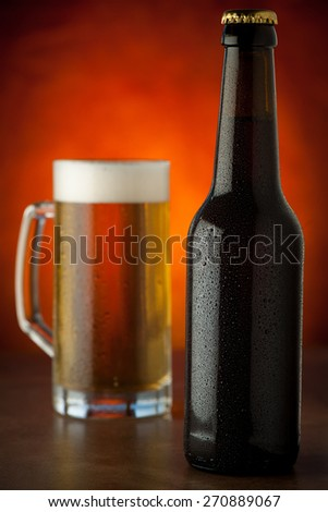Bottle and glass of beer with water drops  served on a stone table - stock photo