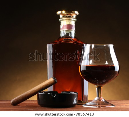 bottle and glass of brandy and cigar on wooden table on brown background - stock photo