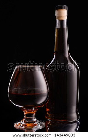 Bottle and glass of cognac over black background - stock photo