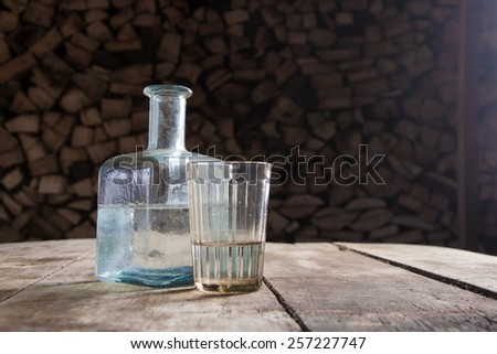 Bottle and glass of moonshine or vodka on the table - stock photo