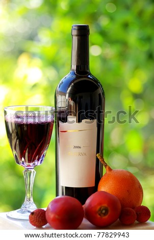 Bottle and glass of red wine and fruits. - stock photo