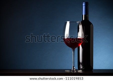 Bottle and glass of red wine on blue background - stock photo