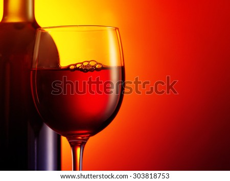 Bottle and glass of red wine on dark red background.Filtered image: warm cross processed vintage effect. - stock photo