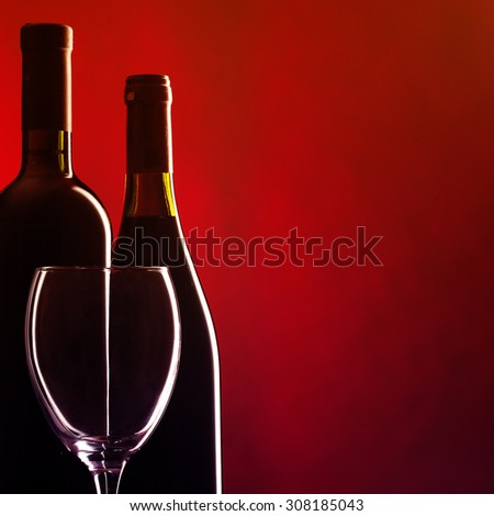 Bottle and glass of red wine on dark red background. Filtered image: warm cross processed vintage effect. - stock photo